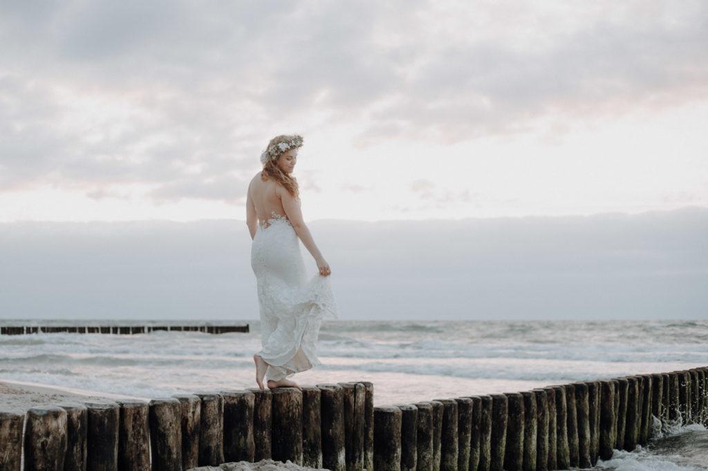Braut tanzt auf den Buhnen am Strand